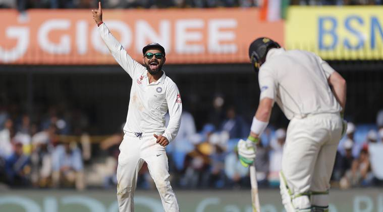 Indian cricket captain Virat Kohli, left, celebrates the dismissal of New Zealand's Martin Guptill, right, during the fourth day of the third test cricket match between India and New Zealand in Indore, India, Tuesday, Oct. 11, 2016. (AP Photo/Rafiq Maqbool)