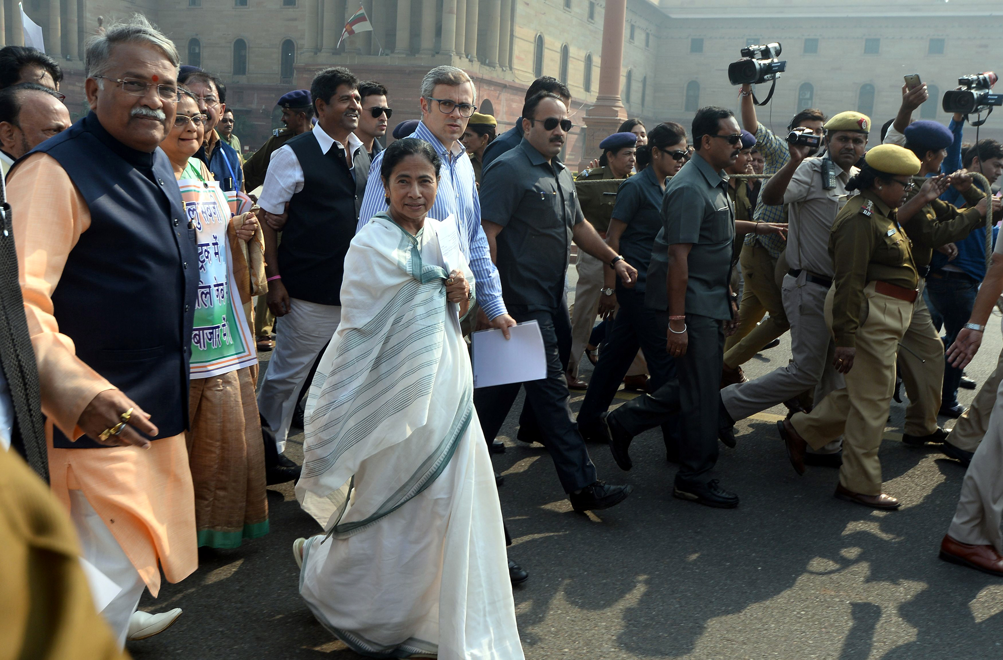 West Bengal Chief Minister and leader of opposition Trinamul Congress (TMC) Mamata Banerjee (C) walks with former chief minister of Jammu and Kashmir Omar Abdullah (back C) and other politician towards the President's House in protest against the removal of high denomination currency notes from circulation in New Delhi on November 16, 2016. Long queues formed outside banks in India since the government's shock decision to withdraw the two largest denomination notes from circulation.  / AFP PHOTO / SAJJAD HUSSAIN