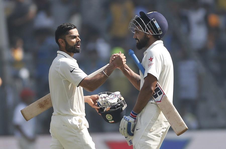 Indian cricket captain Virat Kohli, left, greets Murali Vijay on the third day of the fourth cricket test match between India and England in Mumbai, India, Saturday, Dec. 10, 2016. (AP Photo/Rafiq Maqbool)