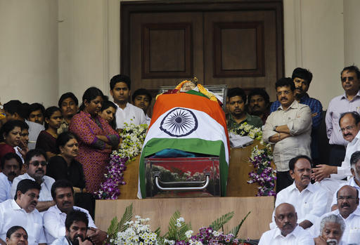 Politicians and friends surround the body of India's Tamil Nadu state former Chief Minister Jayaram Jayalalithaa wrapped in the national flag and kept for public viewing outside an auditorium in Chennai, India, Tuesday, Dec. 6, 2016. Jayalalithaa, the hugely popular south Indian actress who later turned to politics and became the highest elected official in the state of Tamil Nadu, died Monday. She was 68. (AP Photo/Aijaz Rahi)